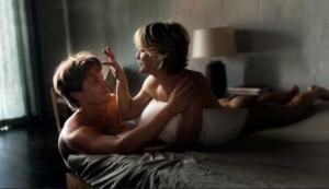 femme cougar dans un lit avec jeune homme